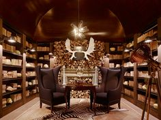 Love everything about this room!  The rustic antlers, the chairs, the bookcases, the fireplace and unique wood surround and the zebra rug. All 100% drool-worthy in my book!