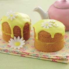 Two mini sponge cakes filled with lemon and topped with lemon icing and daisies