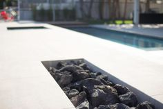 A+modern+fire+pit+is+built+right+in+to+the+concrete+deck+that+surrounds+this+southern+California+pool.+Horizonal+planes+characterize+the+space+and+contribute+to+its+restful,+mod+aesthetic.
