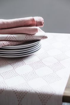 Linen tableware in coral. TIMANTTI Tablerunner, design by Aoi Yoshizawa. Woven in Finland by Lapuan Kankurit.