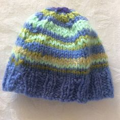 A dear little hat for a new baby or a dolly! Hat knitted in wool. Stripes of blue, aqua and lime - with a touch of cream and purple.