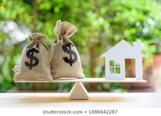 home loan / reverse mortgage or transforming assets into cash concept : house paper model us dollar hessian bags on a wood balance scale depicts a homeowner or a borrower turns properties into cash