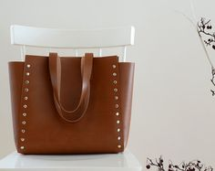 The Squareforma Tote in Brown.  Minimalist and simple, capacious and elegant handmade leather bag will fit everything you need.  It is perfect for work or for the lazy, afternoon trip. Crazy horse leather will be always pleasant and nice in touch. The straps will allow carrying your bag comfortably all day long. Nothing more to add!  DETAILS: • Width: 35 cm • Height: 30 cm • Depth: 11 cm • Strap: 31 cm from center of strap to top edge of bag • Inside open pocket  MATERIALS: Unlined natural…