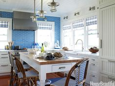 A blue tile backsplash takes over one whole wall in a Fire Island kitchen.
