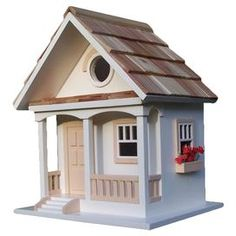 Offer feathered friends a cozy abode with this beautifully crafted birdhouse, showcasing a pine-shingled roof and weather-resistant finish.