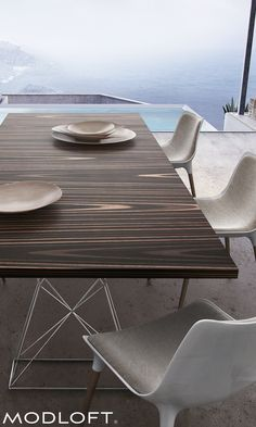 "Modloft Curzon dining table in exotic Brazilian cathedral ebony veneer over stainless steel legs. Also available in Teak finish. Two sizes include 87"" and 102"" lengths. Available in our quick-ship program for immediate delivery. Click to learn more."