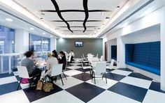In the cafeteria the black and white canvas of the interiors has a shot of colour from banquette seating upholstered in a corporate blue