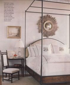 the best of both worlds- iron upholstered canopy bed with sunburst mirror above