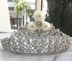 a diamond tiara of baguette and marquise-cut diamonds topped with three large pear-shaped pearls