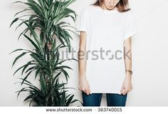 Young girl wearing blank t-shirt. Concrete wall background and green palm close the girl. Horizontal mockup