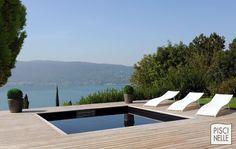 Une piscine semi-enterrée Piscinelle sur les hauteurs du lac d'Annecy... une vraie merveille esthétique qui se joue des contraintes techniques ! Le liner noir apporte un effet miroir à la scène qui est très impressionnant.
