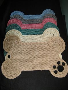 Thick and heavy hand crocheted dog bone shaped floor place mat embellished with black paw print in one corner. Use to place food & water bowls or great for a floor rug.  Large size can accommodate up to 3 bowls. Measures approximately 25 x 18  ** Smaller size also available in my shop; variety of colors  ** Crochet pattern PDF download is also available in my shop for both sizes  COLORS AVAILABLE: Green Pink Tan Blue Grey Ivory Cream Red Orange (not in photo) Yellow Gold (not in photo)…
