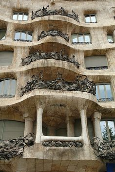Casa Mila by Catalan architect Antoni Gaudi is logic defiant, even hard to frame properly with the camera!. This modernista house is also known as La Pedrera (quarry) Look at that set of irregular balconies with elaborate and impossible ironwork. As you notice, the stone is cut and aligned in such manner that the balcony appears to ondulate, like foamy waves that cast seaweed upon the shore. Of course the seaweed would be the floral adornments in the wrought iron.