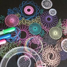 Neon Spirograph drawings on dark paper with Gelly Roll Moonlight pens