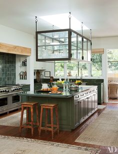 In Ellen DeGeneres and Portia de Rossi's Beverly Hills kitchen, a custom-made glass display case stores tableware. The range is by Wolf, the rugs are antique, and the rustic floor is crafted of reclaimed teak beams from China.