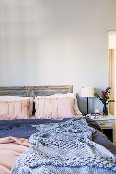 Dormitorio romántico en tonos pasteles, con textiles suaves y respaldo patinado.