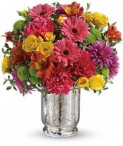 Teleflora's Pleased As Punch Bouquet of colofrul flowers in a mercury glass vase