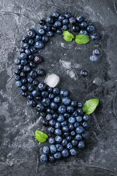 Fresh organic blueberries - Fresh organic blueberries decorated with mint and ice over black stone background. Top view