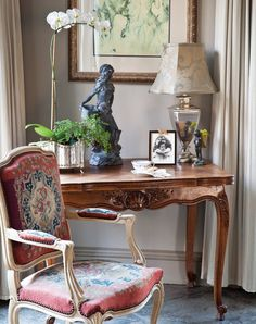 Antique Influence: An array of antiques and florals create a warmly welcoming environment in the guest room, while the desk and needlepoint chair provide a charming space to pen a letter or simply put thoughts to paper.
