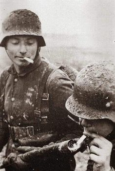 German soldier lights his cigarette with his buddy's flamethrower. Date and location unknown