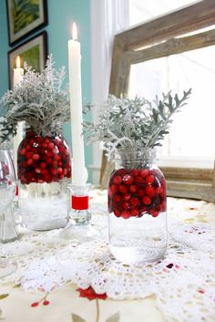 """The centerpieces are just Mason Ball jars that I filled with water, dumped fresh cranberries in, and then stuffed with Dusty Miller from my front garden."" Could use vases"
