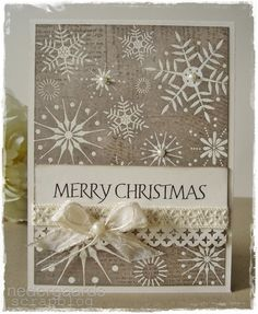 handmade Christmas card from Nedergaard's Scrapblog: Merry Chistmas again .... non-traditional color: kraft ... white embosses snowflackes with pearl centers on three ... collage stamping emboss/resist newspaper print ... bow with ribbon and string on crochet ribbon ... lovely card