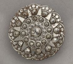 Cut steel coat button made in Birmingham around 1800. This button is part of a set which was probably made for wearing at court and other formal occasions. Birmingham Museum Art Gallery.