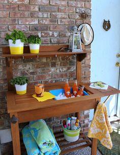 sink a hidden drink bucket into outdoor buffet.  add shelf and hooks above.