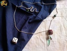 Envoûtant collier Tom Jedusor avec son carnet en pâte fimo légèrement cuivrée, ainsi que sa fiole remplie d'eau verte, en forme de crochet de serpent. Un superbe bijou, à l'image de Tom Jedusor avant qu'il ne devienne Voldemort : séduisant, énigmatique, magique mais aussi sombre.  Page Facebook : http://www.facebook.com/WimeyWibbly?ref=hl N'hésitez pas à liker et partager. Concours Harry Potter en cours pour gagner un lot de 3 créations ! ;)