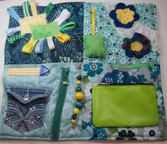 Each of my quilts are made individually by me and are ready for shipping. Every attention to detail is made to bring entertainment, sensory involvement, and fidget useful items with soft fabrics to feel.  This quilt is made with colors of mint green, turquoise blues and navy cotton fabric. The size is 17 x 19. There are lots of activities on the quilt and many fabric to feel. I started with an up cycled jeans pocket for hiding goodies in with added embroidery. Wooden beads on rope roll and…