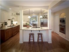 This exquisite kitchen features an island with two paneled posts and pendant lighting for food prep and dining. The posts not only complemen...