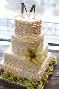 Textured buttercream wedding cake with green flowers and a monogram cake topper (Photo credit: White Dress Photography)