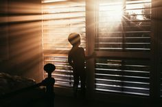 photo of boy looking out a window with streaks of light coming through the blinds by Amy Shire