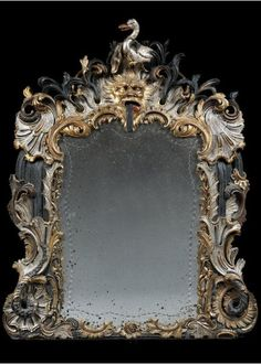 """AN EXTRAORDINARY ROCOCO SILVERED AND GILT CARVED MIRROR WITH GREEN PAINTED WATER EFFECTS CONTAINING CRUSHED SILICA BEARING THE DISTINCTIVE ARMS OF VON GYMNICH, Cologne or Bonn. ca 1740. Height: 37"""" (94 cm), Width: 50 1/4"""" (128 cm) Depth: 5 1/2"""" (14 cm)."""