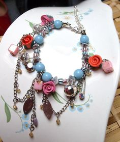 Really pretty charm bracelet with polymer clay roses, plastic and glass beads, chains and silver plastic charms. Very stunning and colourful!    The s