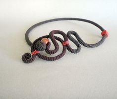 An amazing necklace, very chic and special, consists of 40 (100 cm)  crocheted tube with very fine linen waxed thread in two tone of brown color.  For colored connect I used orange - one wooden and one ceramic beads and little cord. You can wear the necklace with the shape on the front or on the side. There is the closure with crocheted ball like end of the tube and you can run it through whichever hole for different look.    The circumference is around 20(50cm) Original Design by…