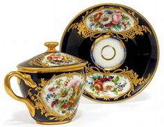 A SEVRES-STYLE PORCELAIN CHOCOLATE CUP, COVER AND STAND <br /><i>CIRCA</i> 1840, KUZNETSOV FACTORY, IRON-RED MARKS <br />With richly-gilt pierced branch handle, painted with bouquets within tooled gilt shaped-oval cartouches issuing diaper panels and flowering branches, on a dark-blue-ground, within gilt line rims (3)<br />