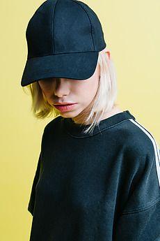 Blonde woman in baseball cap hides eyes by Javier Díez for Stocksy United