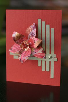 handmade card for the Japanese Floral Art Class at CraftFancy - October 2010  ... luv this dimensional flower fashioned from washi paper ... clean and simple ... like the strips of paper precisely placed at descending heights to frame the card .,. could be woven where they cross, but they're not ... delightful card!!