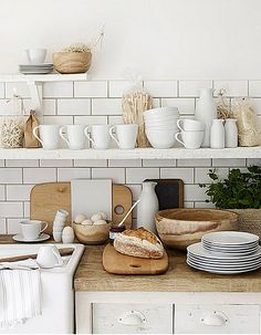 White on white with natural / wood elements. Subway tiles. Shallow open shelves.