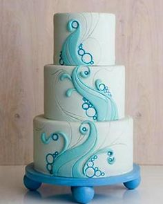 Creative and contemporary, three tier blue beach theme wedding cake with creative blue ocean waves decorations
