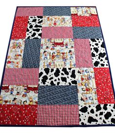 This adorable cowboy patchwork quilt is handmade with patches of cow print, red bandana, blue paisley, red checks, cowboys and cowgirl prints