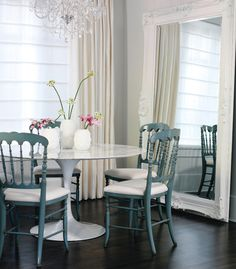 A mix of a modern table with traditional chairs.  Love the mirror & chandelier too.