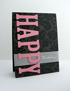 Pink glitter letters bring the HAPPY to this handmade birthday card.  Birthday was stamped with white embossing ink on vellum paper.  Black and grey flourishes on the card base provide a dark background for the bright pink letters.: