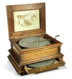 A 15 1/2-inch Polyphon disc musical box, the table model with marquetry inlaid hinged lid and trade label, walnut veneered case, with drawer in the base for disc storage, together with separate pine box containing approximately 50 discs