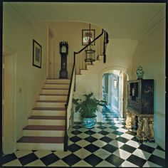 Mark Hampton ~ entrance hall of Louisiana house with black and white marble floors and lacquered chest