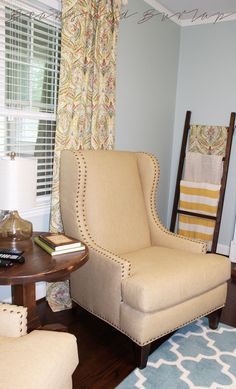 Large pieces of furniture in neutral tones are a great investment to any home! Changing out curtains and accessories are a lot friendly on your budget than new wingback chairs.  See that blanket ladder hidden back there? DIY instructions this weekend on how to build your own!  beansandburlap.blogspot.com  Burlap  |  Nailhead Trim  |  Wingback Chair  |  Blanket Ladder