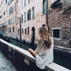 i sit on the railing, along a water way alley in europe. Its just another day of the week abroad. Taking in the architecture, reading my book and drinking some coffee.