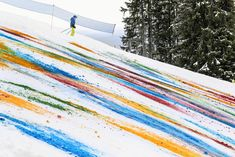 using food coloring, breuning splashes and pours the liquid chroma onto the surface of snow, allowing it to slide and swivel down the sloping snowy pathway.
