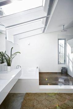 The sun pours through the skylight into the bathroom, which has a cantilevered long basin and straight-sided two-metre bath for two, both made by Marblecast (marblecast.co.za). A duckboard floor from Wood Kraut was fitted for extra comfort. The grass rug is from Ashanti Design (ashantidesign.com).